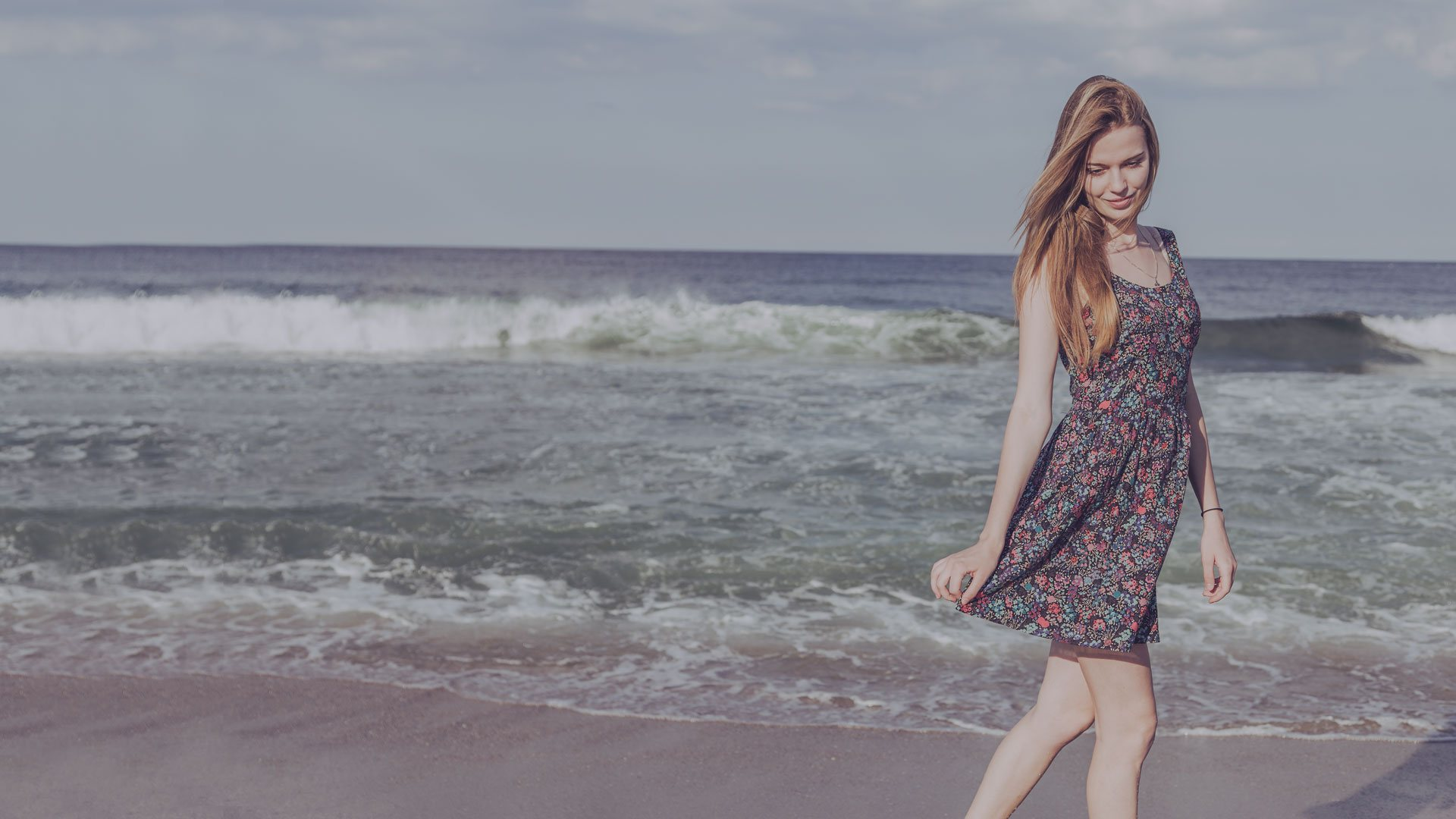 Woman walking on a beach with a summer dress, small waves in the background