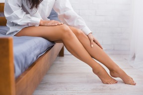 Woman sitting on bed and touching her legs