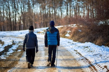 two people walking on a snowy path