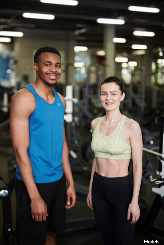 Man and woman in the gym wearing workout clothes
