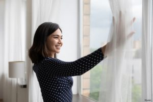 Woman opening her curtains
