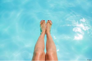 person with their feet in the pool